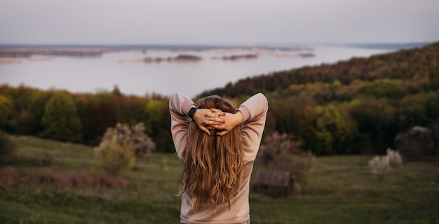Молодая девушка стоит спиной со светлыми волосами и руками над головой.
