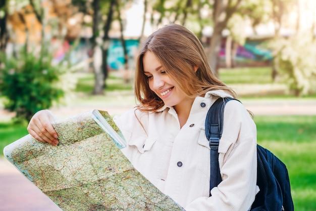 若い女子学生が地図を持って街を歩き回り、道を探しています。交換学生のコンセプト