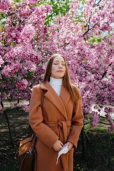 少女はマスクを脱いで、パンデミックの終了後、晴れた春の日、咲く庭の前で深呼吸します。保護と防止のcovid 19。