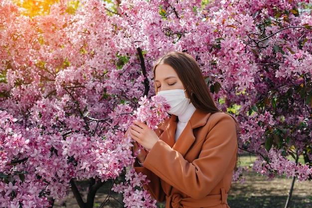 어린 소녀는 그녀의 마스크를 벗고 화창한 봄 날, 만개 한 정원 앞에서 유행성 질병이 끝나면 깊은 숨을 쉰다. 보호 및 예방 covid 19.