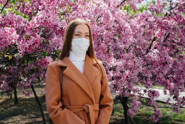 Молодая девушка снимает маску и глубоко дышит после окончания пандемии в солнечный весенний день перед цветущими садами. защита и профилактика ковид-19.
