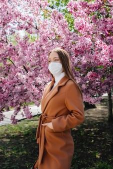 Молодая девушка снимает маску и глубоко дышит после окончания пандемии в солнечный весенний день на фоне цветущих садов. защита и профилактика covid 19.