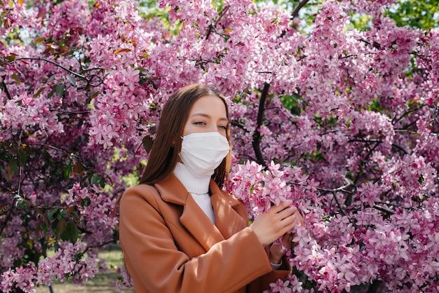 Молодая девушка снимает маску и глубоко дышит после окончания пандемии в солнечный весенний день перед цветущими садами.