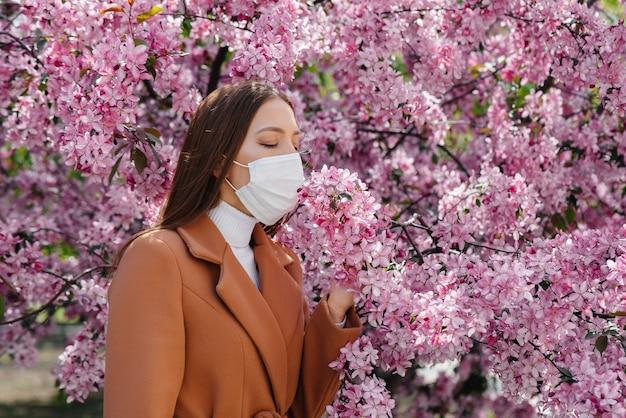 Молодая девушка снимает маску и глубоко дышит после окончания пандемии в солнечный весенний день