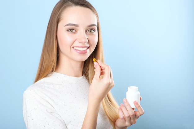 어린 소녀는 오메가 캡슐 건강 관리 영양 보조제를 섭취합니다