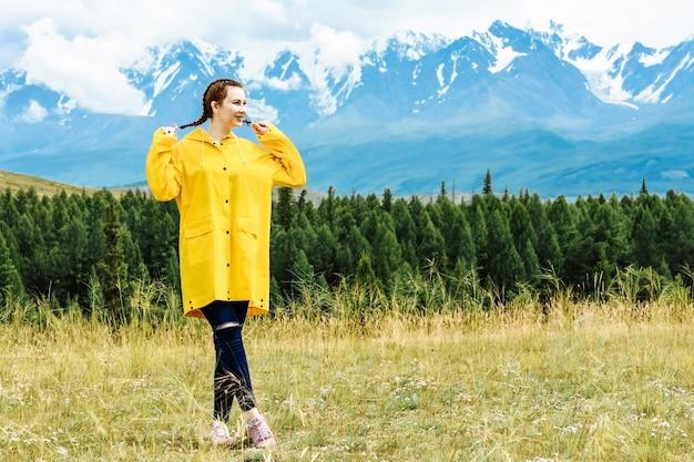 어린 소녀 관광은 눈 덮인 산의 배경에 선다. 여행 및 휴가 개념