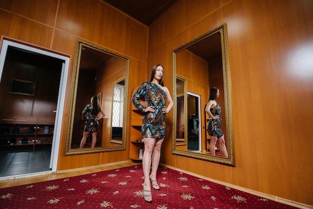若い女の子が店の試着室で新しい服を試着します。