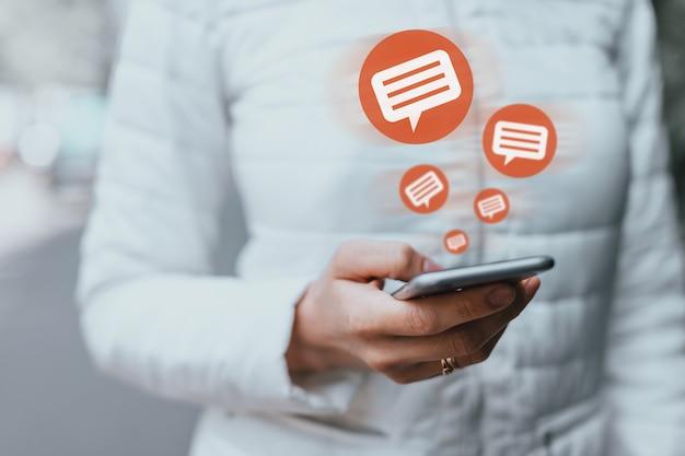 Молодая девушка с помощью смартфона получает комментарии и сообщения в социальных сетях.