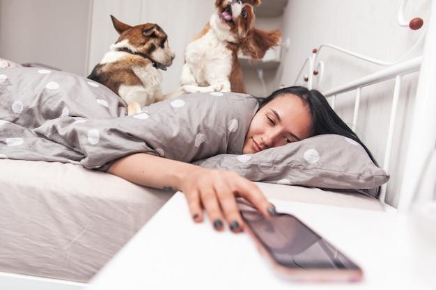 Молодая девушка просыпается в своей постели и выключает будильник. собаки разбудили своего хозяина