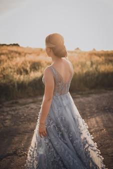 若い女の子は、日没時に灰色の青いロングドレスでアスファルト道路に沿って歩きます。背中と腕が開いています