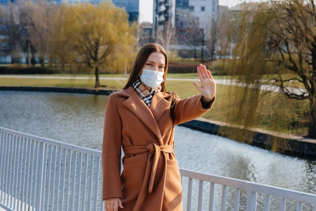 パンデミックとコロノウイルスの最中に、少女がマスクの中を歩きます。