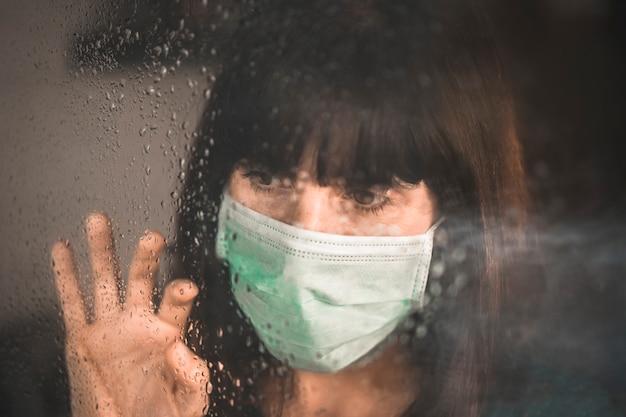 Молодая девушка в маске в пандемии covid-19, положив руку на окно и просматривая