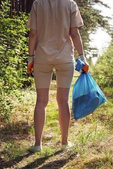 장갑을 끼고 있는 어린 소녀가 가방에 쓰레기를 수집합니다. 생태 재해로부터 환경을 구합니다. 자원 봉사자, 환경 운동가 개념.