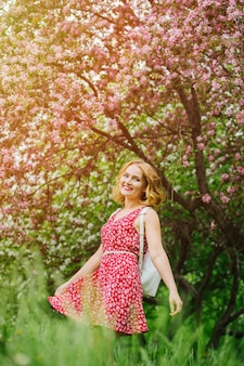 Молодая девушка с рюкзаком в яблоневом саду
