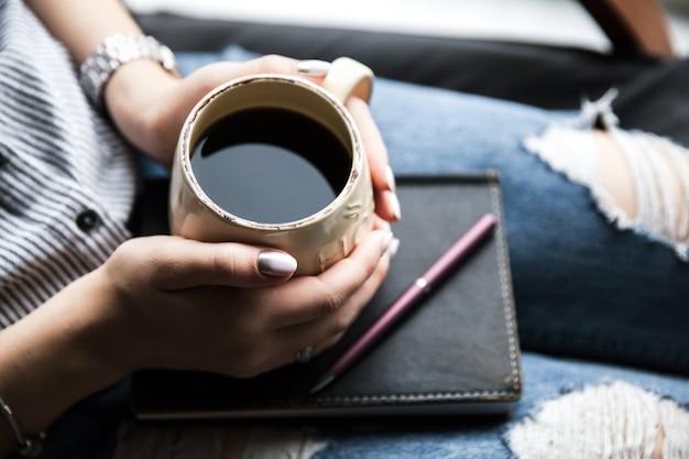 美しいマニキュアを持った少女が一杯のコーヒーで本を持っています。ファッションスタイル