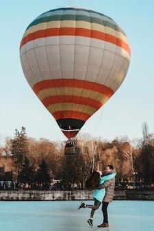 公園の風船を背景に氷の上に立っている男の子と若い女の子。