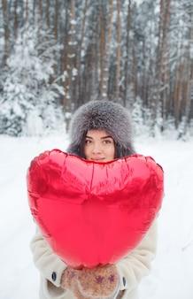 Молодая девушка с ярким воздушным шаром в форме сердца стоит в заснеженном лесу. день святого валентина. на зимние каникулы.