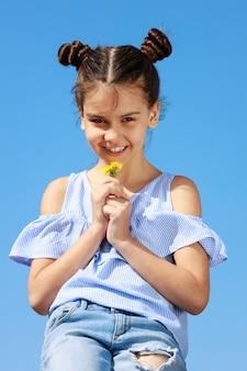 青い空を背景にタンポポを手にした少女。高品質の写真