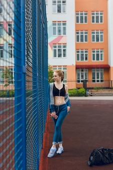 良い体型の少女がスタジアムの青いフェンスの近くに立っています。彼女は黒のトップと青いスポーツスーツを着ています。彼女はヘッドフォンで音楽を聴いています。