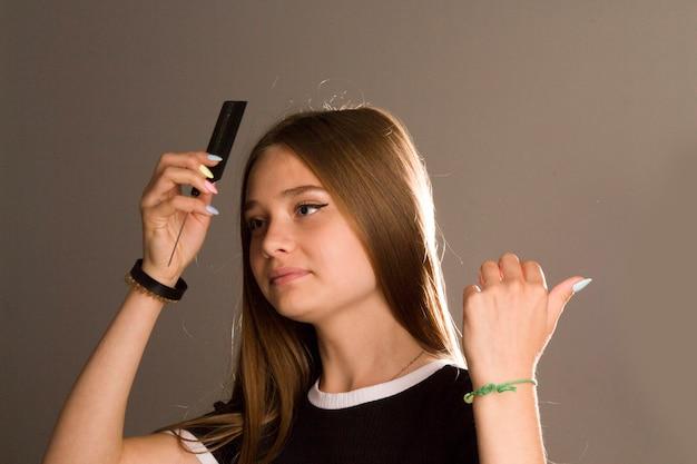 빗을 든 어린 소녀. 젊은 미녀 빗 굵고 긴 건강한 갈색 머리와 미소, 개념-모발 관리