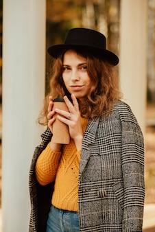 Молодая девушка в шляпе и кофе расслабляется в осеннем парке