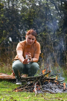 Молодая девушка с термосом для горячего кофе или чая сидит на дереве. прогревание у костра в лесу.