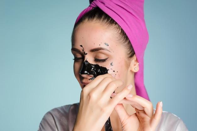 ピンクのタオルを頭にかぶった少女が顔から黒いクレンジングマスクを外す