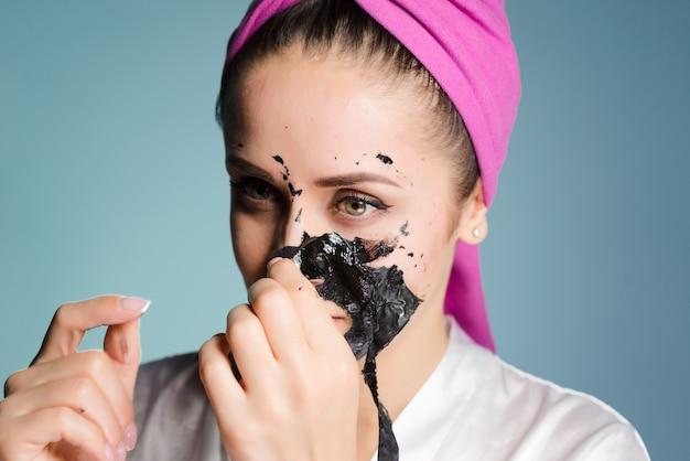 ピンクのタオルを頭にかぶった少女が顔から黒いマスクを外す