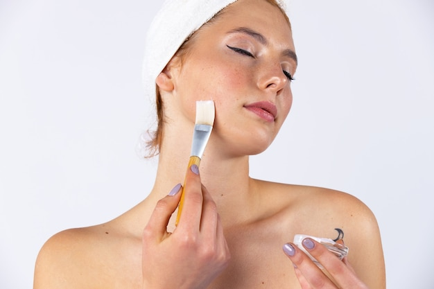 그녀의 머리에 수건을 걸고 매달려있는 어린 소녀가 브러시로 젤 마스크를 적용합니다. 아름다운 외모를 가진 유행 여성 모델. 흰 벽에 사진. 고품질 사진