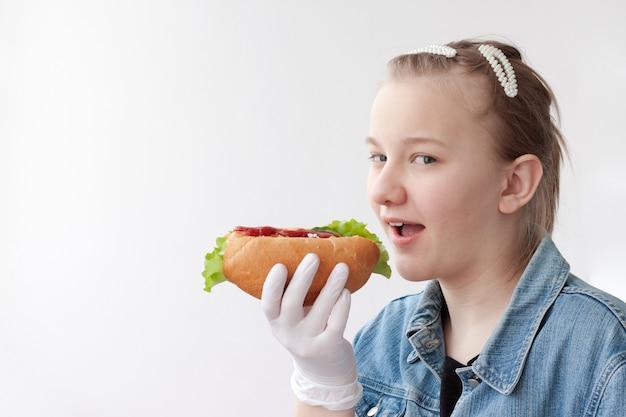 青いデニムのジャケットと医療用手袋をはめたブロンドの髪の少女は、開いた口の前でホットドッグを持って、一口食べたいと思っています。