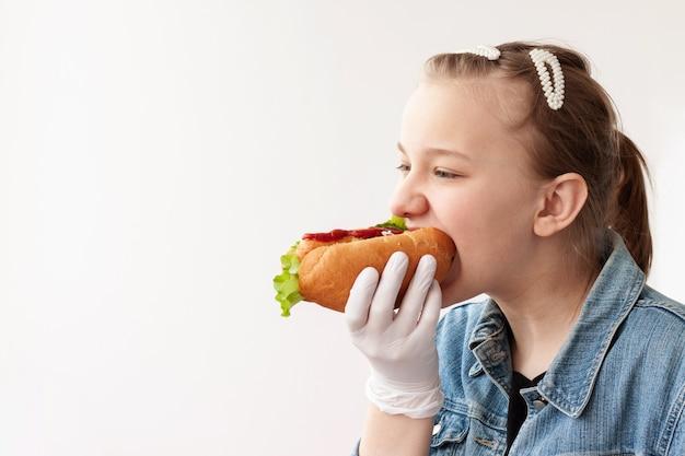 青いデニムのジャケットと医療用手袋をはめたブロンドの髪の少女が、ホットドッグを持って噛んでいます。