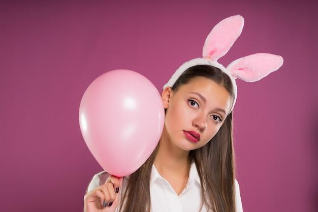 ウサギの耳を持つ少女は、膨らませてピンクのボールを持って、カメラをじっくりと見ています。ピンクの背景に分離