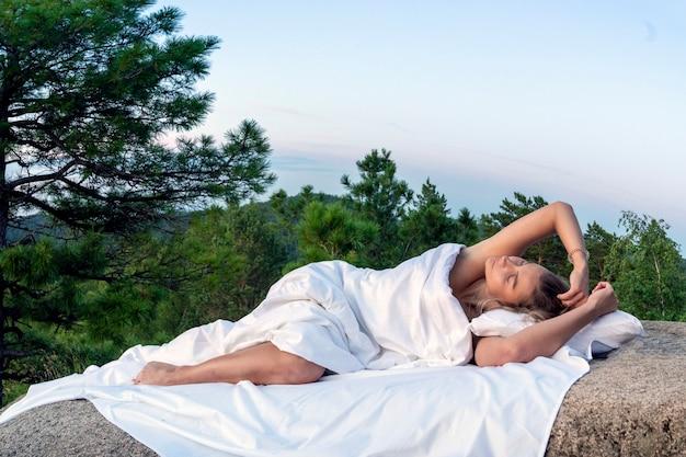 Молодая девушка-женщина спит на белой простыне в лесу на камнях из коры в постели, крупный план. сон и комфорт, постельное белье. кровать и уют на природе. лето или осень