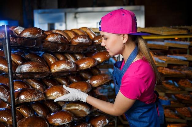 若い女の子がパン屋で働いています。彼女は棚にパンを置きます。パン屋の職場で女性パン屋。プロのパン屋がパンを手に持っています。パンの生産コンセプト