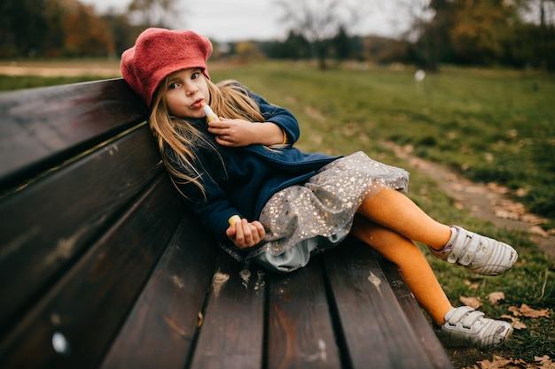 ベンチでポーズをとる若い魅力的な女の子