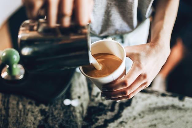 Молодая симпатичная блондинка в повседневном стиле держит стакан и вспениватель молока в уютной кофейне. .