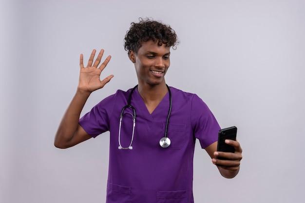Молодой симпатичный темнокожий врач-мужчина с вьющимися волосами в фиолетовой форме со стетоскопом смотрит на свой смартфон, машет рукой