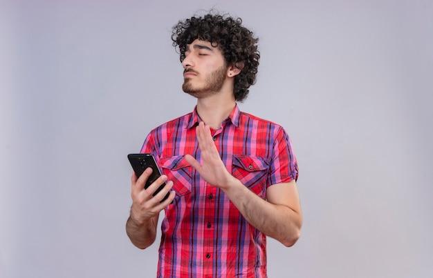 Молодой красивый мужчина с вьющимися волосами в клетчатой рубашке, закрывая глаза, держит мобильный телефон