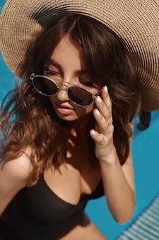 夏の日に屋外のプールでポーズをとる黒い水着、帽子、流行のサングラスで官能的な完全な唇と完璧なメイクをした若いゴージャスな女性。