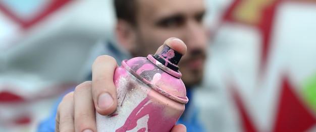 Молодой художник граффити в синем пиджаке держит банку с краской