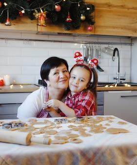 Молодые бабушка и внучка обнимаются на кухне во время приготовления печенья в канун рождества.