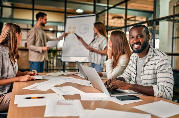 Группа молодых людей обсуждает новый бизнес-план на доске, работает на ноутбуках, сидя в современном офисе.
