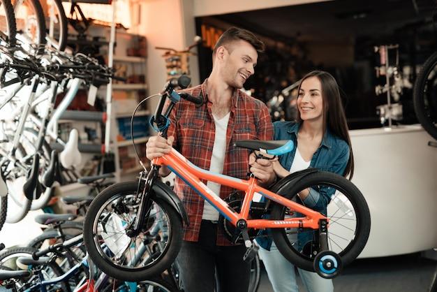 젊은 남자와 여자가 어린이 자전거를 선택하고 있습니다.