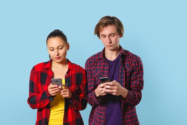 格子縞のシャツを着た若い男と女が並んで立って、スマートフォンを見ています。青い背景に