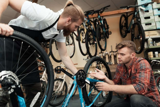 Молодой парень пришел в мастерскую, чтобы починить велосипед.