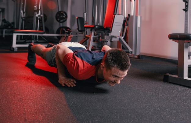 한 젊은 남자가 운동을하는 동안 체육관 바닥에서 팔 굽혀 펴기를합니다. 건강한 생활. 집중 훈련