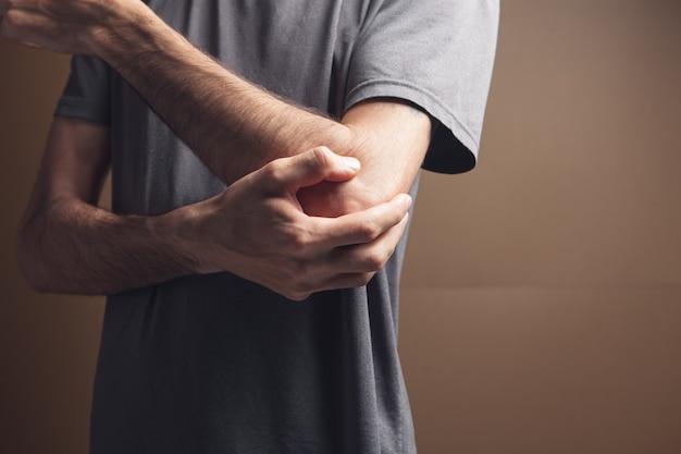 젊은 남자는 갈색 배경에 아픈 팔꿈치가 있습니다