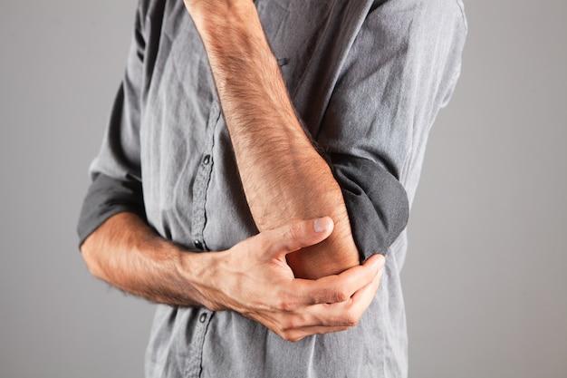 젊은 남자는 회색 배경에 아픈 팔꿈치가 있습니다