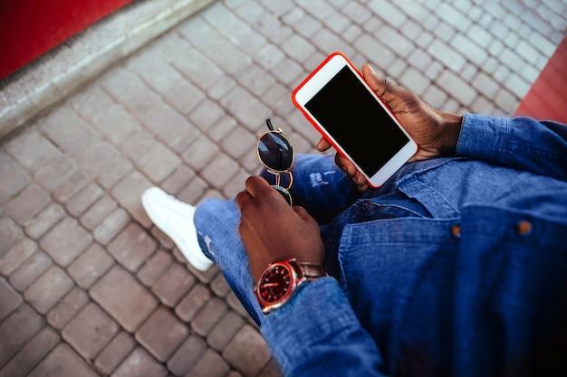 Молодой парень держит мобильный телефон на улице