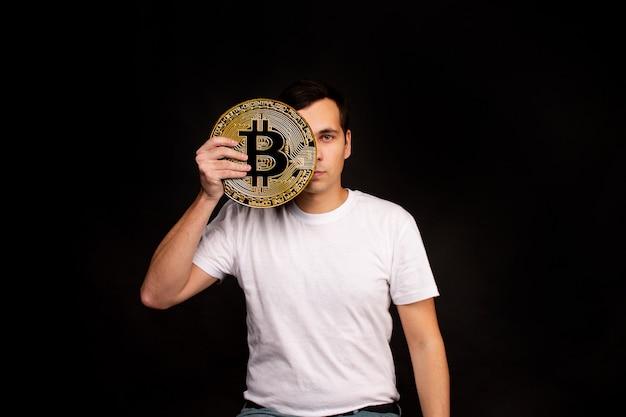 若い男がビットコインのシンボルを持っています、ビットコインは交換と購入のための現代的な通貨です